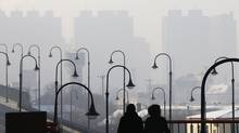 Pedestrians walk as haze partially obscures a view of downtown Harbin, Heilongjiang province, January 6, 2014. A new study shows that pollution from Chinese heavy industry is drifting across the Pacific and affecting air quality on the west coast of North America. (Kim Kyung Hoon/REUTERS)