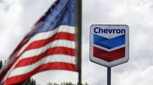 In this May 23, 2013, file photo, a United States flag flies in view of a Chevron gas station in Blaine, Wash. (Elaine Thompson/AP)