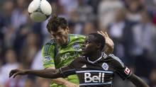 Vancouver Whitecaps FC Gershon Koffie, right, fights for control of the ball with Seattle Sounders FC Brad Evans during first half MLS soccer action in Vancouver, Saturday, Sept. 29, 2012. (JONATHAN HAYWARD/THE CANADIAN PRESS)