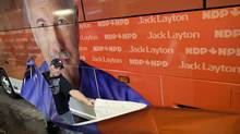 Jordan Blancher applies adhesive wrap covering to a Canada Coach charter bus for NDP leader Jack Layton March 23, 2011 in preparation for a looming federal election. (Moe Doiron/Moe Doiron/The Globe and Mail)