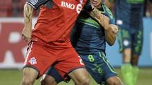 Toronto FC's Torsten Frings battles for the ball against Santos Laguna's Juan Pablo Rodriguez (MIKE CASSESE/REUTERS)