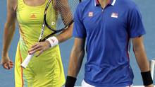 Novak Djokovic and Ana Ivanovic of Serbia share a laugh in their match (STRINGER/AUSTRALIA/REUTERS)