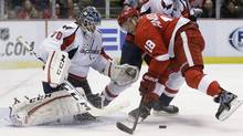 Detroit Red Wings centre Joakim Andersson tries controlling the puck in front of Washington Capitals goalie Braden Holtby during the second period of an NHL hockey game in Detroit, Friday, Nov. 15, 2013. (Associated Press)