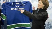 B.C. Liberal Leader Christy Clark is presented with a hockey jersey by former NHL player Dave Babych during a campaign stop in North Vancouver on April 28, 2013. (Jonathan Hayward/The Canadian Press)