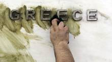 A worker cleans graffiti off the Bank of Greece logo, outside the central bank's headquarters in Athens, Monday, Nov. 26, 2012. (Thanassis Stavrakis/AP)