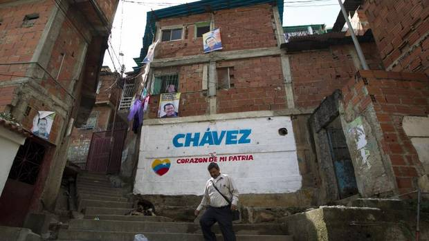 A man walks past campaign posters of Venezuelan President Hugo Chavez in Caracas on Saturday. Venezuelans go to the polls on Sunday in a presidential election that pits Mr. Chavez against opposition rival Henrique Capriles. (Carlos Garcia Rawlins/REUTERS)