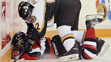 Kingston Frontenacs' Brent Mackie checks Ottawa 67's' Pat Daley battles into the boards, during first period OHL action, in Ottawa on Friday Oct. 21, 2005. There was no penalty called on the play. (Jana Chytilova)