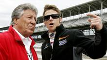 Driver Marco Andretti (R) and his grandfather Mario Andretti talk in the pit lane on the last day of practice before the Indianapolis 500 at the Indianapolis Motor Speedway in 2008. (BRENT SMITH/Reuters)