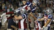 Montreal Alouettes' Sean Whyte (top C) is lifted by teammates after his winning field goal during the second half of their CFL football game against the Hamilton Tiger-Cats in Montreal August 23, 2012. (Reuters)