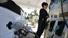 A resident looks at the price of gasoline as she fuels up her car at a gas station in South Beach in this file photo. (CARLOS BARRIA/REUTERS)