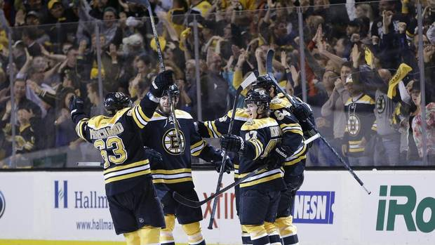 Boston Bruins left wing Brad Marchand (63), right wing Nathan Horton, second from left, and defenceman Torey Krug (47) celebrate a goal by defenceman Adam McQuaid (54) during the third period of Game 4 in the Eastern Conference finals of the NHL Stanley Cup playoffs against the Pittsburgh Penguins, in Boston on Friday, June 7, 2013. (Elise Amendola/AP)