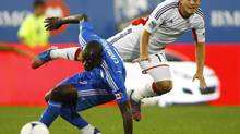 Montreal Impact's Hassoun Camara and New England Revolution's Kelyn Rowe (R) battle for the ball during the first half of their MLS match in Montreal, July 18, 2012. (OLIVIER JEAN/REUTERS)