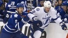 Toronto Maple Leafs Colby Armstrong (L) rides Tampa Bay Lightning's Adam Hall into the boards in the first period of their NHL hockey game in Toronto April 5, 2012. (FRED THORNHILL/REUTERS)