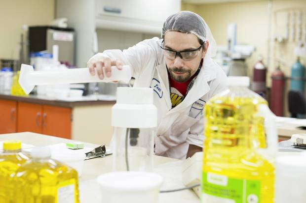 Richardson Oilseed is one of Canada's oldest and largest fully-integrated crushing, refining, processing and packaging operations of Canola and its products. A worker in the company's test lab is shown checking a sample of canola oil.