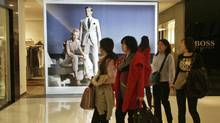 Women walk past a Hugo Boss store at a shopping mall in Beijing March 17, 2010. (Jason Lee/Reuters)