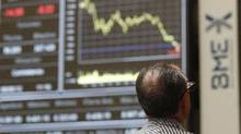 A trader views electronic boards at the stock exchange in Madrid, June 8, 2012. (Andrea Comas/REUTERS)