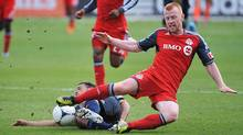 Toronto FC Richard Eckersley, right, goes down while battling Philadelphia Union Danny Cruz for the ball during the second half of a soccer game in Toronto Saturday September 15, 2012. (The Canadian Press)