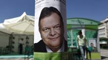 A pre-election poster of leader of Socialist PASOK party Venizelos is seen on a pole in front of a campaign kiosk in Athens June 12, 2012. (Yorgos Karahalis/REUTERS)