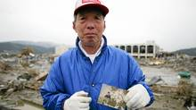Tsuyoshi Kinno, 73, holds a picture of a missing friends son and daughter at a weddings in Rikuzen-Takaata, Miyagi Prefecture, Japan March 14, 2011. Thousands of people died in this small town 70 km north east of Sendai. (Boaz Arad/Boaz Arad)