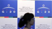 A woman walks past the press centre for the G20 finance ministers and central bank governors who met earlier this year in Busan, South Korea. (JO YONG-HAK)