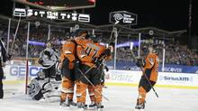 The Anaheim Ducks celebrate a goal by right wing Corey Perry as Los Angeles Kings goalie Jonathan Quick, lower left, sits on the ice during the first period of an NHL outdoor game at Dodger Stadium in Los Angeles, Saturday, Jan. 25, 2014. (Chris Carlson/AP)