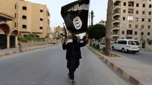 A member loyal to the Islamic State in Iraq and the Levant waves an ISIL flag in Raqqa on June 29, 2014. (REUTERS)