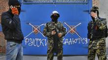 "Pro-Russian militants stand in front of a gate with graffiti reading ""Russ. Russian do not surrender"" in Slavyansk, eastern Ukraine, on April 25, 2014. (SERGEI GRITS/ASSOCIATED PRESS)"