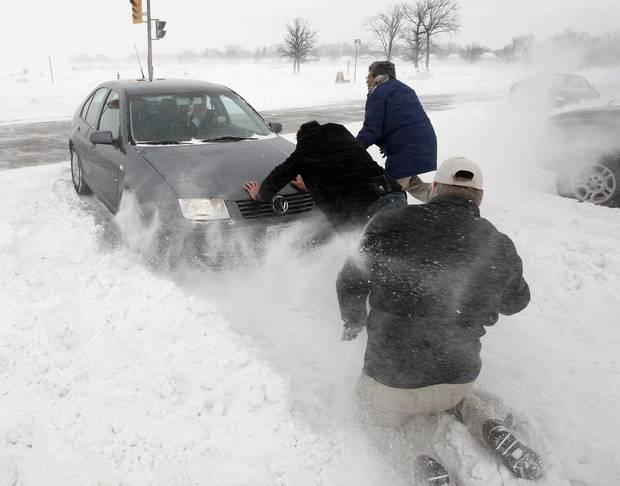 Good samaritans help a driver entering a snow-clogged Mount Royal Road in Winnipeg on Jan. 25, 2010.