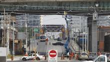 Crews looked at the underside of the Gardiner Expressway in Toronto last summer, after another chunk of concrete fell onto the roadway below. (Peter Power/The Globe and Mail)