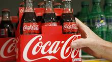 An employee arranges bottles of Coca-Cola at a store in Alexandria, Va., October 16, 2012. (KEVIN LAMARQUE/REUTERS)