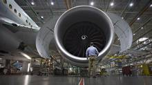 A worker stands in front of an engine on the Boeing 777 at the company's assembly operations in Everett, Wash., Oct. 18, 2012. The company has already cut $2.2-billion in costs since 2010. (ANDY CLARK/REUTERS)