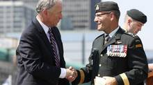 Canada's Defence Minister Rob Nicholson, left, shakes hands with Lieutenant-General Marquis Hainse, the new commander of the Canadian Army, during a change of command ceremony on Parliament Hill in Ottawa July 18, 2013. (CHRIS WATTIE/REUTERS)