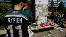 Tyler Stychyshyn wears a Manitoba Moose jersey as he pauses at a makeshift memorial for former Vancouver Canucks hockey player Rick Rypien Aug 17, 2011. (DARRYL DYCK/THE CANADIAN PRESS)