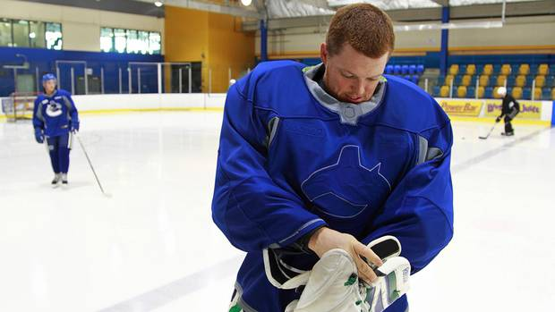 Cory Schneider of the Vancouver Canucks adjusts his gear after turning his practice jersey inside out during an informal skate at UBC in Vancouver September 18, 2012. (Jeff Vinnick/The Globe and Mail)