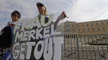 Demonstrator holds an anti-Merkel banner prior to a protest in front of the Greek Parliament in Athens on Tuesday Oct. 9, 2012. German Chancellor Angela Merkel makes her first visit to Greece since the euro zone crisis began three years ago. (Lefteris Pitarakis/AP)