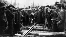 Donald A. Smith, later Lord Strathcona, drives home iron spike at Craigellachie, B.C. at 9:22 a.m. on Nov. 7, 1885, completing the CPR transcontinental line. With him are Sandford Fleming (left, top hat and white beard) and W.C. Van Horne (hand in pocket, black beard). (Ross, Best & Co. / CPR Archives / NS1960)