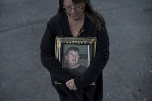 Paulette Raymond cradles a photo of her late brother Tommy while posing in Halifax on Oct. 21, 2017. Mr. Raymond was killed in a work-related accident in 2009.