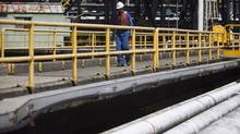 A Kinder-Morgan employee makes his way past various pipes including crude oil pipeline leading from Alberta at the Kinder Morgan Westridge marine terminal in Burnaby, British Columbia, Sunday, July 8, 2012. (Rafal Gerszak For The Globe and Mail)