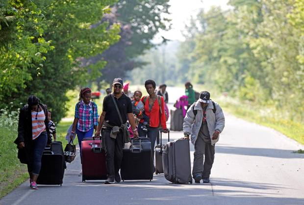 Three families that claimed to be from Burundi walk down Roxham Road to cross into Quebec at the U.S.-Canada border in Champlain, N.Y.