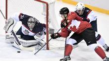 Canada's Corey Perry is stopped by United States' goaltender Jonathan Quick as Team USA's Cam Fowler (3) moves in during first period hockey semi-final action at the 2014 Sochi Winter Olympics in Sochi, Russia on Friday, February 21, 2014. THE (Nathan Denette/THE CANADIAN PRESS)