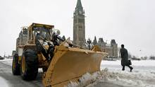 A snow plow clears slush around Parliament Hill amid heavy rain in Ottawa on March 10, 2011. (Sean Kilpatrick/The Canadian Press)