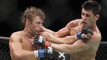Urijah Faber, left, trades punches with Dominick Cruz during the first round of their UFC bantamweight mixed martial arts title match, Saturday at The MGM Grand Garden Arena in Las Vegas. (Eric Jamison/Associated Press)
