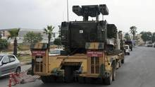A Turkish military truck transports a mobile missile launcher on Wednesday to the Syrian border, in Iskenderun, Turkey. Turkey is deploys antiaircraft units along its border with Syria after the downing of one of its warplanes by Syrians. (Associated Press)