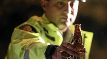 RCMP Constable Faz Majid removes an open bottle of beer from a motorist's car during a roadside check in Surrey, B.C. (DARRYL DYCK/THE CANADIAN PRESS/DARRYL DYCK/THE CANADIAN PRESS)