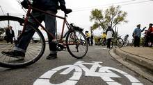 A cyclists walks by a bike lane symbol painted by activists at a memorial on Monday, November 14, for pregnant cyclist Jenna Morrison, who was killed after being struck by a truck at Sterling and Dundas in Toronto. (Michelle Siu/The Globe and Mail/Michelle Siu/The Globe and Mail)
