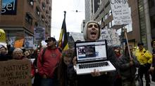 Niko Salassidis chants as he streams a live video of the Occupy Toronto protest he is taking part in Toronto, Ont. on October 16, 2011. Peaceful protests began yesterday inspired by the Occupy Wall Street movement in New York City and protesters have set up camp at Saint James Park near Toronto's financial district. (Michelle Siu/The Globe and Mail/Michelle Siu/The Globe and Mail)