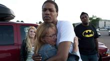 Judy Goos hugs her daughter's friend, Isaiah Bow, 20, while eyewitnesses Emma Goos, 19, left, and Terrell Wallin, 20, right, gather outside Gateway High School where witnesses were brought for questioning Friday. (Barry Gutierrez/AP)