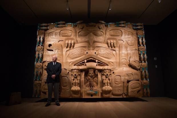 Michael Audain stands in front The Dance Screen (The Scream Too) – an enormous cedar dance screen by Haida master carver James Hart.