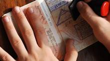 A hand holds down a page of a passport while it is stamped. (Taolmor/Thinkstock)