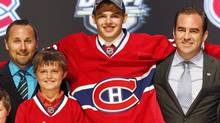 Alex Galchenyuk, centre, smiles with officials from the Montreal Canadiens after being chosen third overall in the first round of the NHL hockey draft on Friday, June 22, 2012, in Pittsburgh. (Keith Srakocic/AP)